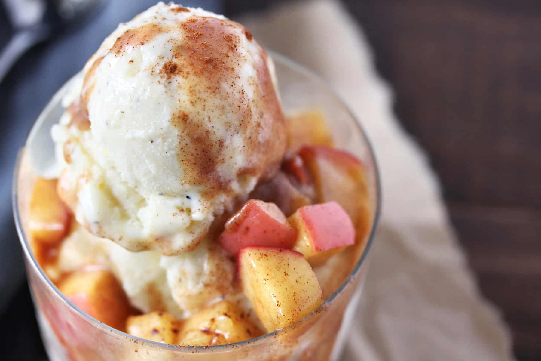 Vanilla ice cream with cinnamon apple topping in a clear glass on grey napkin.
