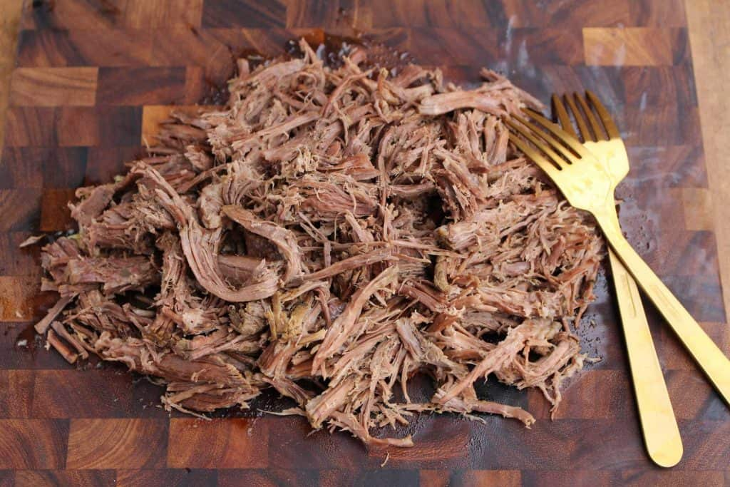 Shredded beef on cutting board with two forks.