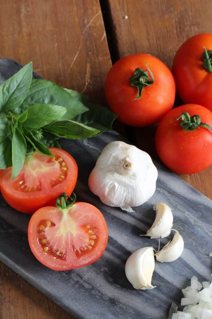 Tomatoes, basil, garlic and onion on blue cutting board.