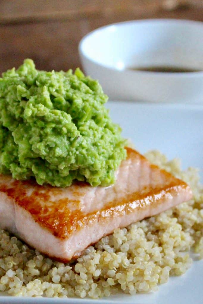 Edamame Avocado Mash with Salmon and Sesame Ginger Sauce on white plate.