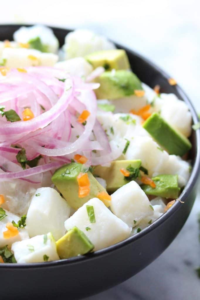 Fish, avocado and red onion in black bowl.