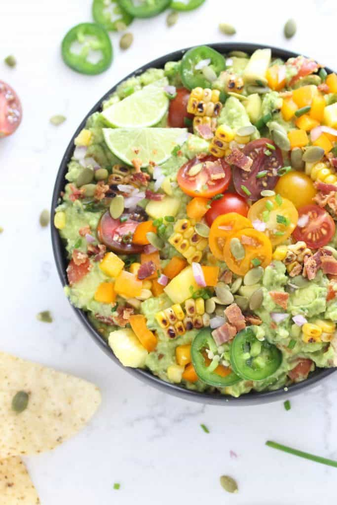 Guacamole in black bowl with corn, tomatoes, jalapeños and bacon