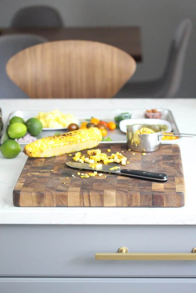 Corn and knife on brown cutting board on white counter.