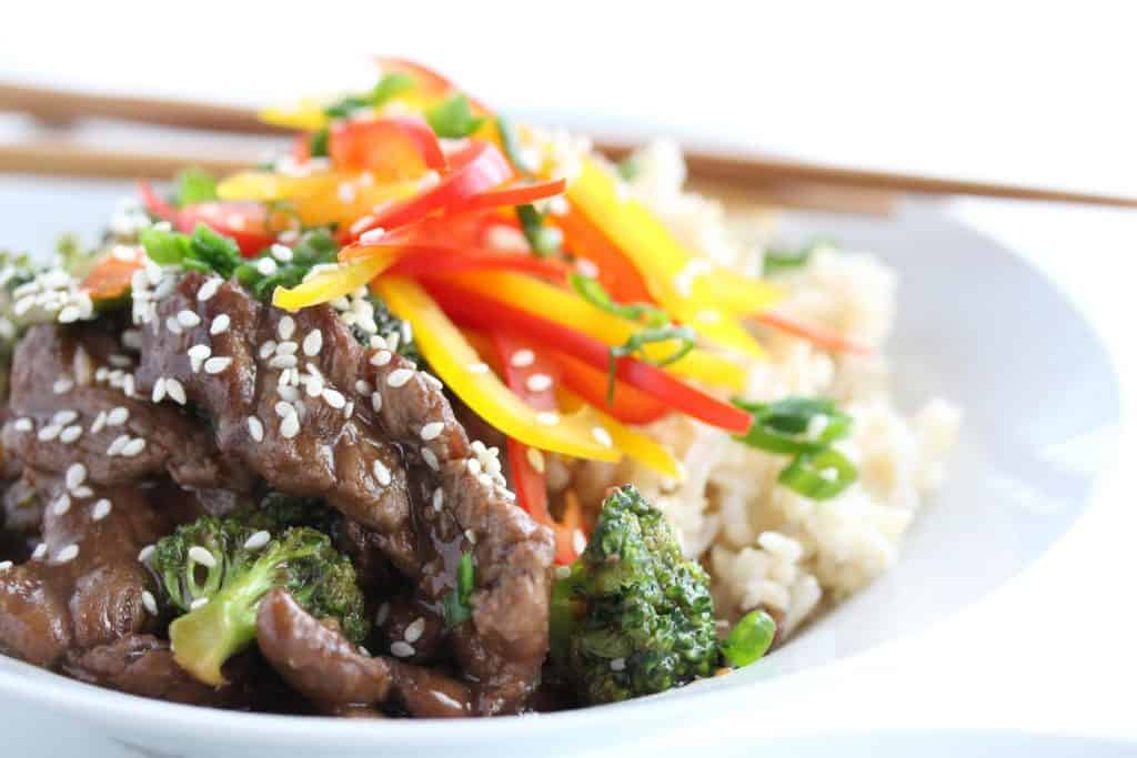 Beef and broccoli stir fry in white bowl with chopsticks.