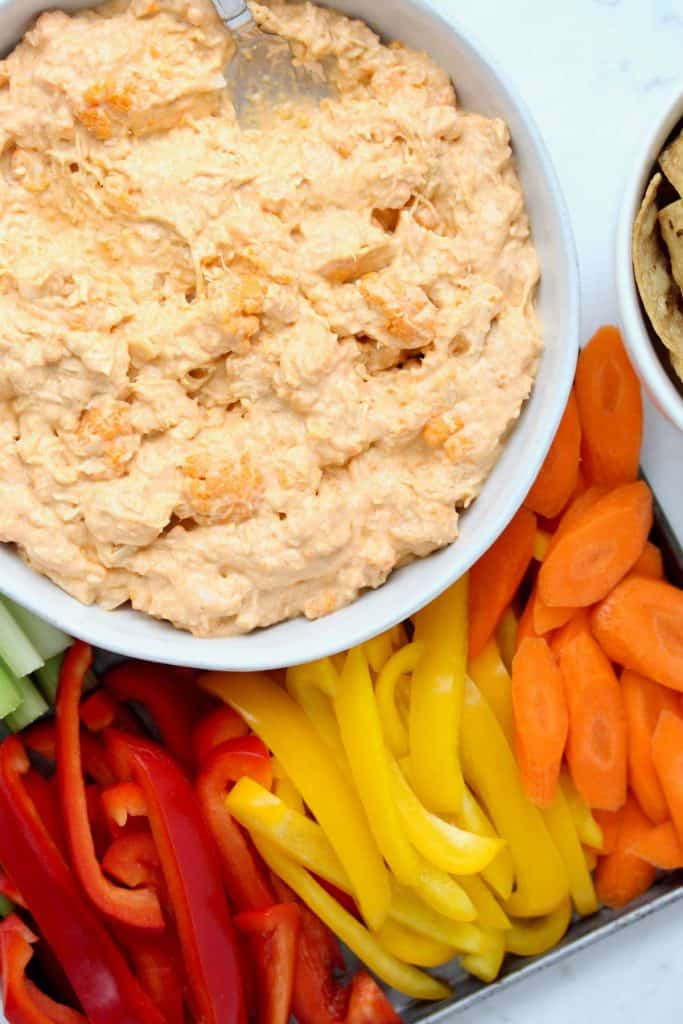 Buffalo dip in white bowl with sliced vegetables.