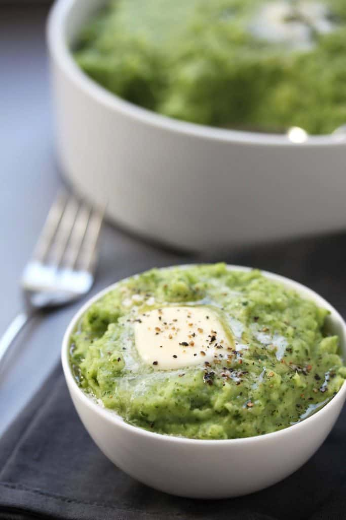 Spinach mashed potatoes in a white bowl on grey napkin.