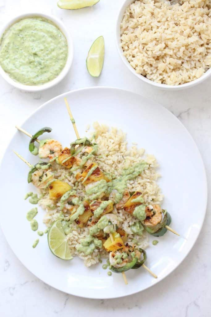 Shrimp skewers and rice on white plate.