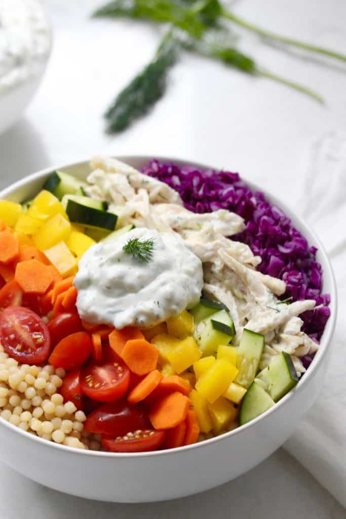Fresh veggies, couscous and chicken in white bowl with Tzatziki sauce.