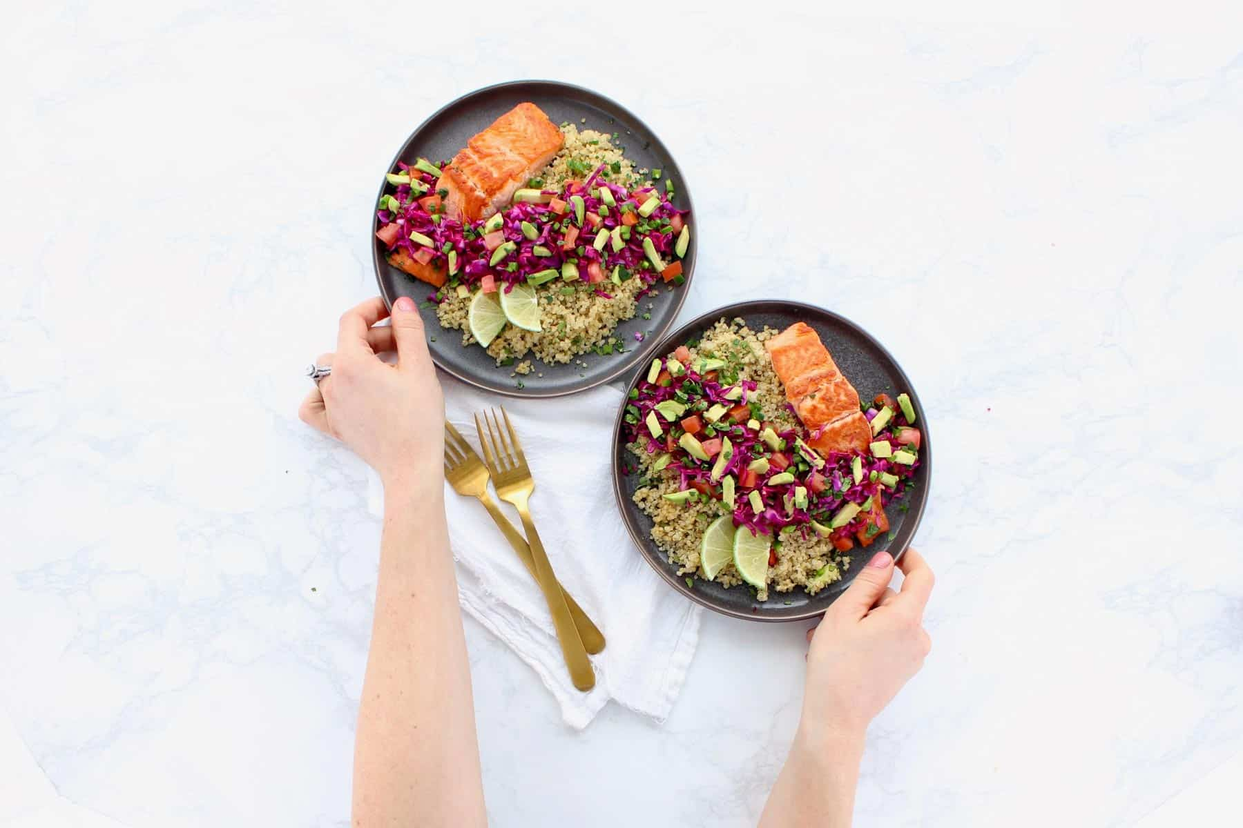 Salmon, quinoa and fresh vegetables on two grey plates.