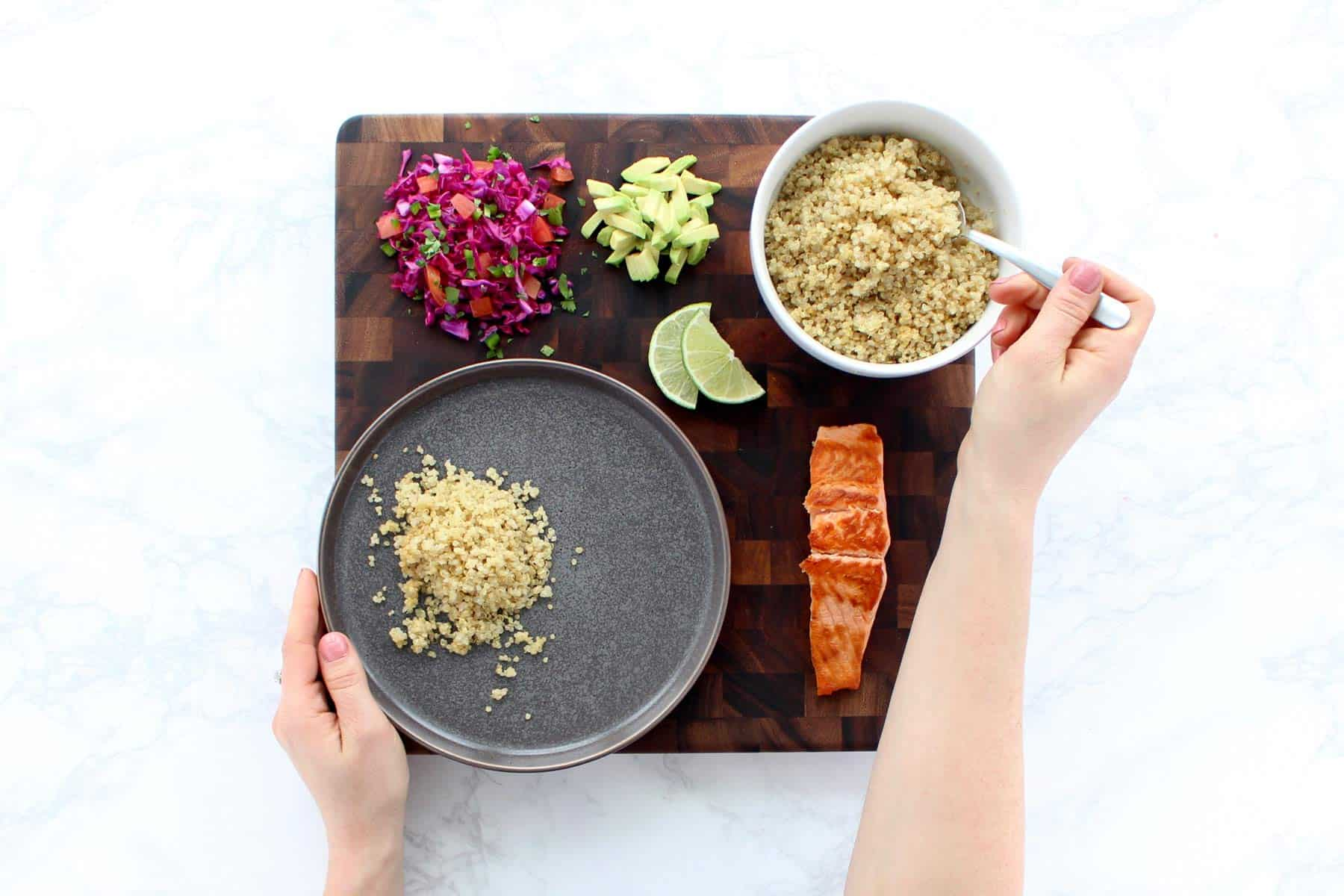 Two hands assembling salmon and rainbow quinoa recipe.
