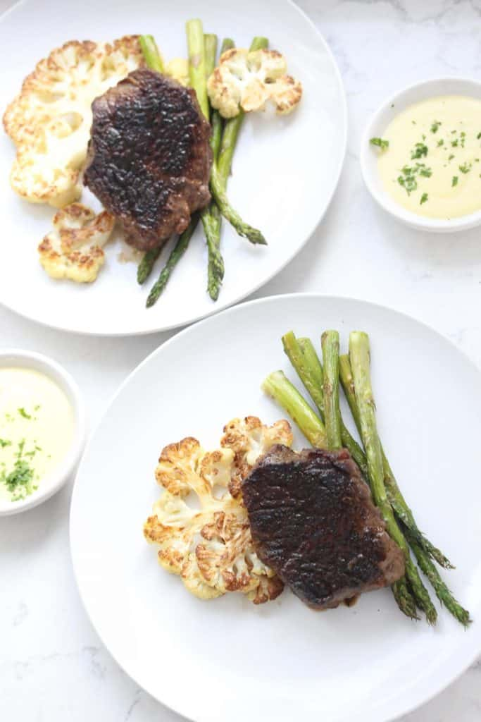 Steak, cauliflower and asparagus on a white plate with hollandaise.