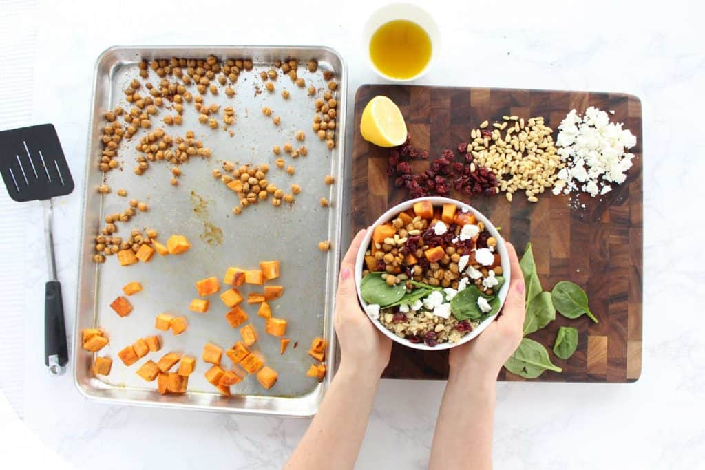 Two hands holding sweet potato and quinoa salad in white bowl.